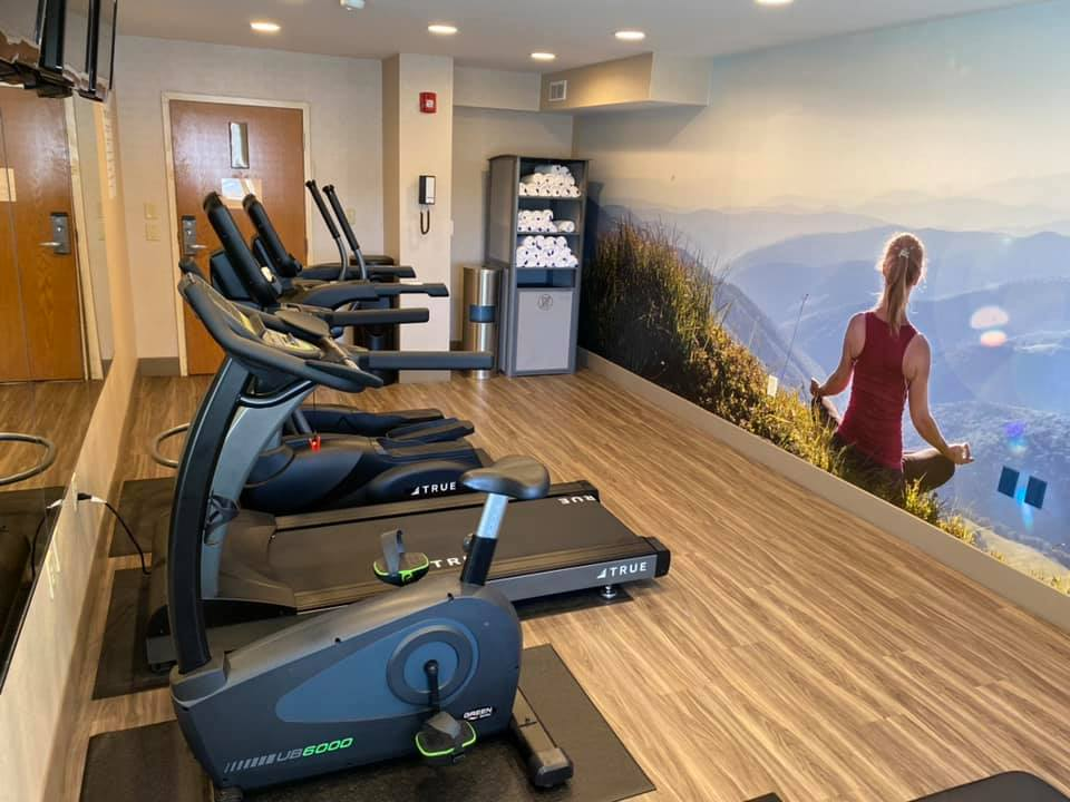a picture of the fitness center at the newly renovated Clarion Pointe Harrisonburg featuring a wall mural of a woman meditating on a mountaintop, one treadmill, one elliptical, one exercise bike. 3 televisions, and more.