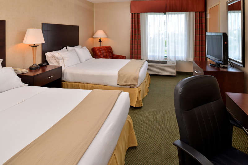 a picture of the Holiday Inn Express & Suites in Ocean City, MD showing a guest room with two queen size beds