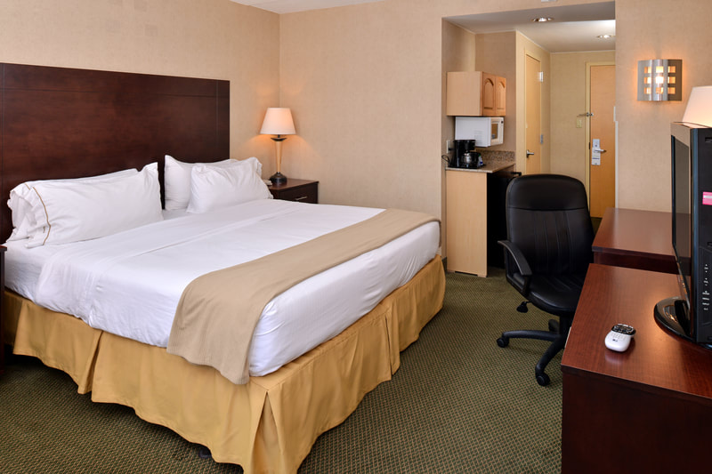 a picture of the Holiday Inn Express & Suites in Ocean City, MD showing a guest room with one king sized bed