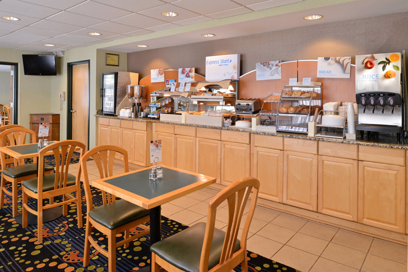 a picture of the breakfast area at the Holiday Inn Express & Suites in Ocean City, MD including our complimentary breakfast options of cinnamon rolls, pancakes, eggs, and juice and more