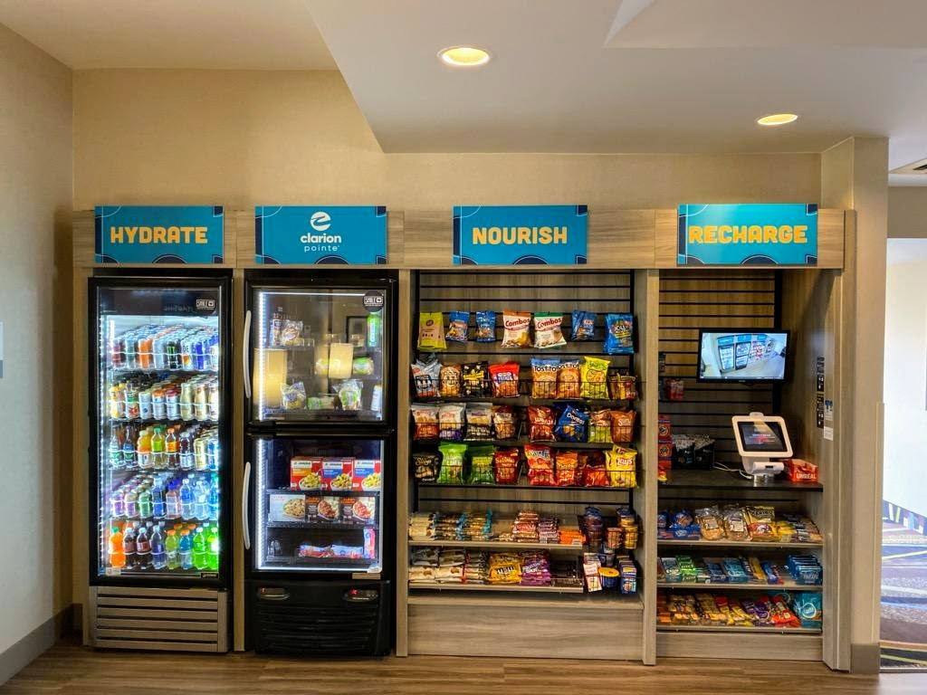 a picture of the lobby convenience store at the newly renovated Clarion Pointe Harrisonburg featuring self checkout, craft beers, and wine; in addition to sodas, snacks, ice cream, sundries, and more
