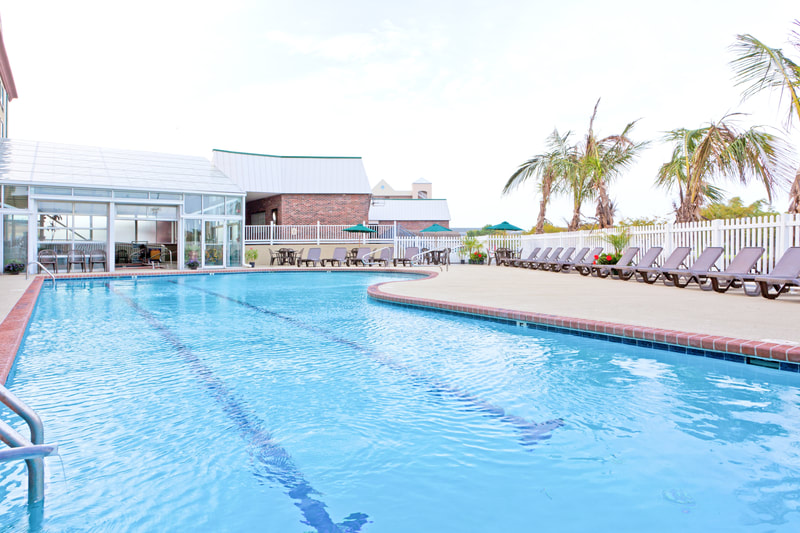 a picture of the Holiday Inn Express & Suites in Ocean City, MD showing the outdoor pool and indoor pool with sundeck