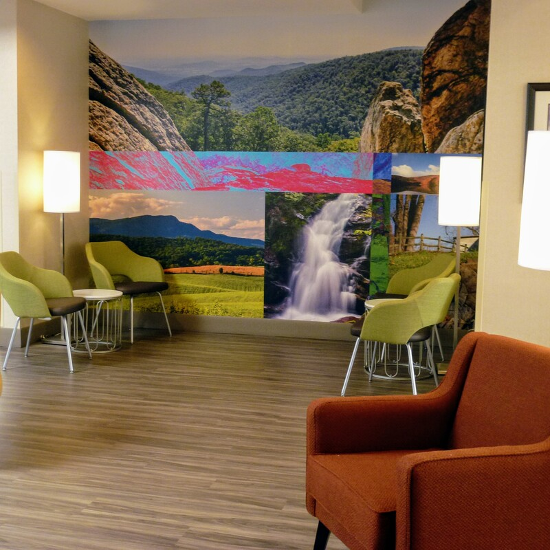 a picture of the lobby at the newly renovated Clarion Pointe Harrisonburg featuring a wall mural showing an assortment of local photography